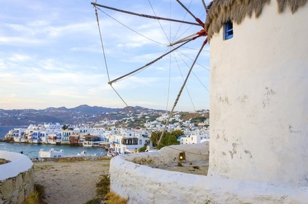 myconos: A windmill in Chora, Mykonos, Greece. Very traditional greek whitewashed architecture, a popular landmark and tourist destination on the island of winds against the deep blue sky and the Aegean sea overlooking Little Venice. The wind mills are now decorat Stock Photo