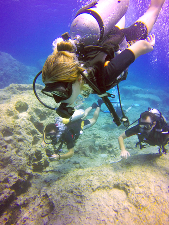 Young scuba divers, woman, man swimming underwater. View of the scuba diver gear, tank, regulator, mask, fins and bubbles in the deep blue sea of Protaras, Cyprus. Stock Photo