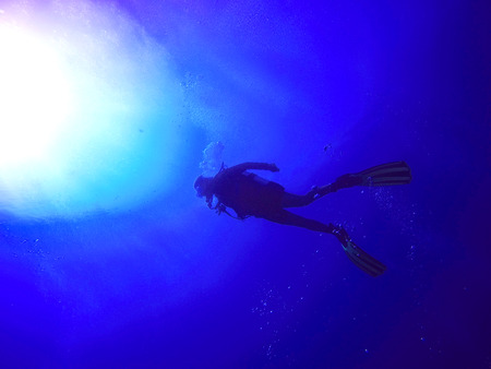 A backlit scuba diver silhouette. View of the scuba diver gear, fins and bubbles underwater in the deep blue sea of Limassol, Cyprus against the sunlight. Stock Photo