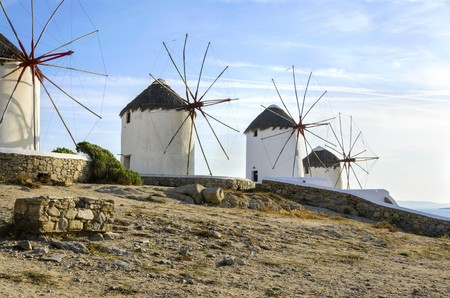 Four windmills in Chora, Mykonos, Greece. Very traditional greek whitewashed architecture, a popular landmark and tourist destination on the island of winds against the deep blue sky and the Aegean sea. The wind mills are now decorative.