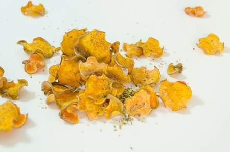 A pile of homemade baked sweet potato chips stacked over. A healthy sweetpotato vegetarian crisp snack seasoned with oregano and olive oil, isolated against white background.