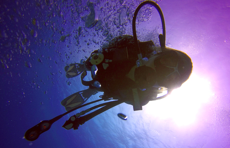 A backlit scuba diver silhouette. View of the scuba diver gear, fins, regulator, mask and bubbles underwater in the deep blue sea of Limassol, Cyprus against the sunlight.