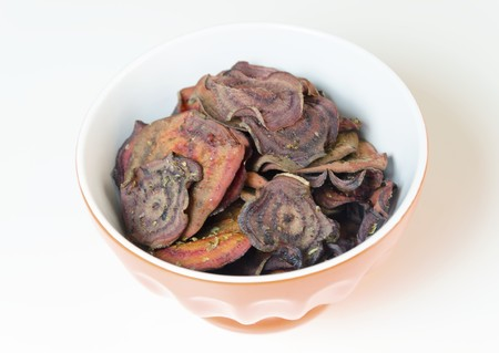 Thin round beetroot chips baked in the oven with oregano and salt and ripe beet roots in a bowl isolated on white background. A healthy, vegetarian, vegan, crispy snack appetiser for diet and clean eating.