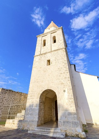 The pyramidal tower of the Church of our Lady of Health, a romanesque cathedral formely named St Michael the archangel, basilica at the Square of the The Glagolitic housed monasteries on Krk island, in Croatia. Stock Photo