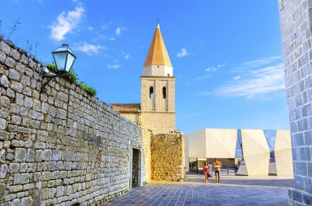 The pyramidal tower of the Church of our Lady of Health, a romanesque cathedral formerly named St Michael the archangel, basilica at the Square of the The Glagolitic housed monasteries on Krk island, in Croatia and the elementary school mirrors. Stock Photo