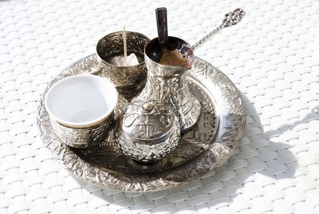 A metallic tray with copper plated cezve (d�ezva) filled with traditional foam Bosnian coffee, a silver pot with turkish delight, rahat lokum, a clay cup and sugar cube pot served in an ornament Sarajevo set.