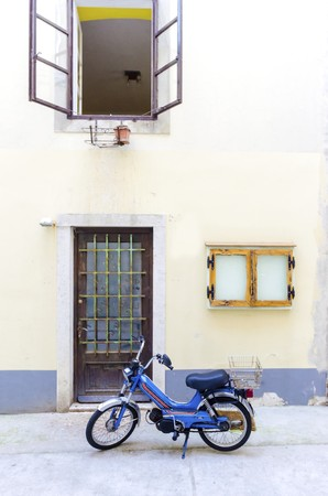 Traditional old Krk town architecture. View of door and open window and old tomos retro automatic motorcycle parked outside at the medieval ancient capital centre.