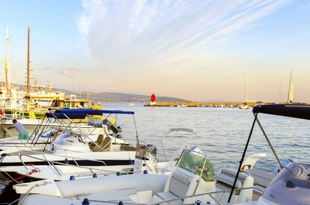 The red lighthouse, mole at Krk town, Croatia marina and boats docked at the harbour pier at sunset. A small cylindrical tower at the biggest port of the island.