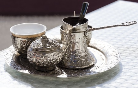 A metallic tray with copper plated cezve (d?ezva) filled with traditional foam Bosnian coffee, a silver pot with turkish delight, rahat lokum, a clay cup and sugar cube pot served in an ornament Sarajevo set.