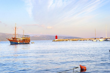 The red lighthouse, mole at Krk town, Croatia, boats docked at the harbour pier and a sail boat entering at sunset. A small cylindrical tower at the biggest port of the island. Stock Photo