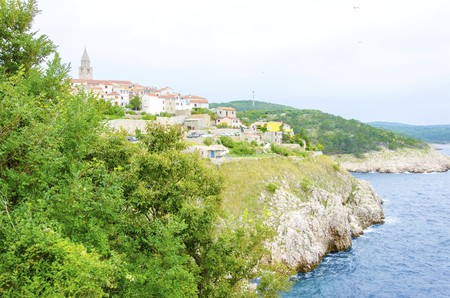 Vrbnik town on Krk island, Croatia. View of Mediterranean medieval architecture, the bell tower of the  Parish church of the assumption of the blessed virgin mary, beach, coastline, sea, rocky cliffs and architecture.