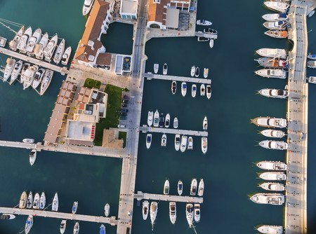 colonade: Aerial view of the beautiful Marina in Limassol city in Cyprus, the boats lined up, piers, and commercial area from above. A very modern, high end and newly developed space where yachts are moored and its perfect for a waterfront promenade.