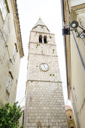 The renaissance bell tower of the Parish Church of the Assumption of the Blessed Virgin Mary in Vrbnik town, Krk, Croatia. A medieval spire with a clock and historic religious monument and landmark.
