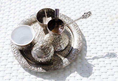 A metallic tray with copper plated cezve (džezva) filled with traditional foam Bosnian coffee, a silver pot with turkish delight, rahat lokum, a clay cup and sugar cube pot served in an ornament Sarajevo set. Stock Photo