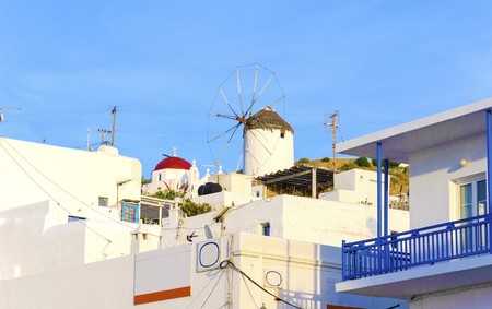 greek island: A very traditional view of the architecture in Chora, on the greek island Mykonos, Greece. A blue door, fence and windows, outside a whitewashed house and a traditional windmill and greek orthodox church with red dome.