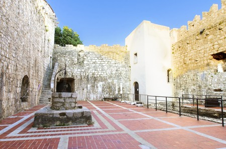 The interior of the Frankopan Castle, at Kamplin square in Krk, Croatia - Frankopanski Kastel, part of the medieval city walls. View of the courtroom, the well, stern, square tower and archer loop holes.