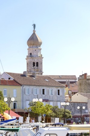 apses: Krk town, Croatian island. View of the port and the bell tower of the Church of the Assumption of Blessed Virgin Mary with an angel holding a trumpet and ceramic tiles on the roof houses.