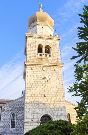 apses: Bell tower of the cathedral, the Church of the Assumption of Blessed Virgin Mary, in Krk, Croatia, a monument of Romanesque era St. Quirinus and Barbara, with a Venetian sculpture of an angel holding a trumpet on top.