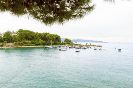 The port on the old town of Krk in Croatia, county Primorje-Gorski Kotar. A view of the Adriatic sea, boats docked, the coast of the island Veglia and part of the city walls. Stock Photo