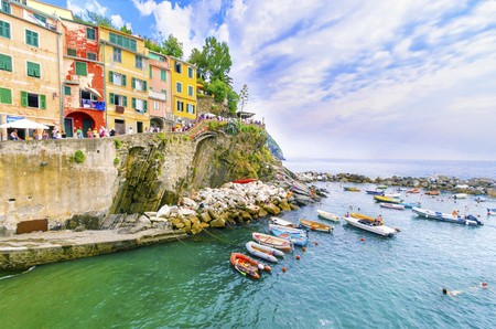 Riomaggiore village, La Spezia province, Liguria, northern Italy. View of the colourful houses on steep hills, sea rocks, beach, laundry on balconies, boats and tourists. Part of the Cinque Terre National Park and a UNESCO World Heritage Site.