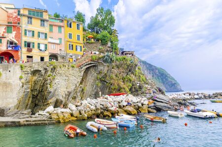 Riomaggiore village, La Spezia province, Liguria, northern Italy. View of the colourful houses on steep hills, sea rocks, beach, laundry on balconies, boats and tourists. Part of the Cinque Terre National Park Editorial