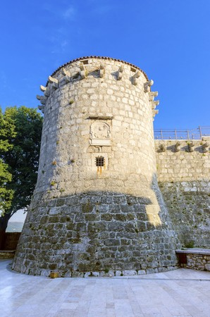 The round venetian tower of Frankopan Castle, at Kamplin square in Krk, Croatia - Frankopanski Kastel and plate with a winged Venetian lion, the symbol of St. Mark. Part of the medieval city walls.
