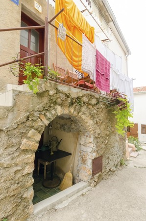 Traditional picturesque Mediterranean architecture at medieval town Vrbnik on Krk island, Croatia. View of stone houses, arched narrow alley, balcony and flowers. Stock Photo