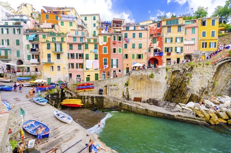 Riomaggiore village, La Spezia province, Liguria, northern Italy. View of the colourful houses on steep hills, sea rocks, beach, laundry on balconies, boats and tourists. Editorial