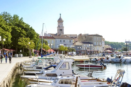 apses: Krk town port, Croatian island. View of the harbour, boats docked at marina and the bell tower of the Church of the Assumption of Blessed Virgin Mary with an angel holding a trumpet. Editorial