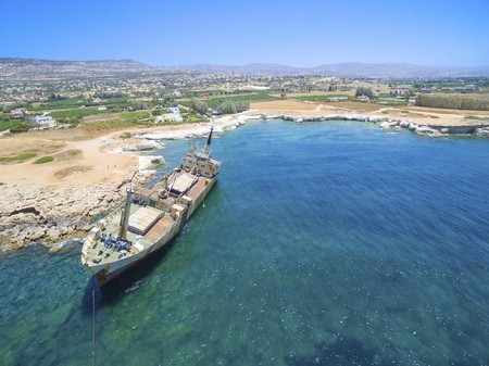 metalic: Aerial view of the abandoned ship wreck EDRO III in Pegeia, Paphos, Cyprus. The rusty shipwreck is stranded on the Peyia rocks at the kantarkastoi sea caves near Coral Bay in Pafos, standing at an angle near the shore. Stock Photo