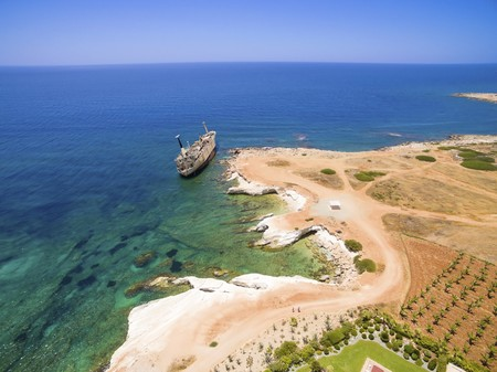 george: Aerial view of the abandoned ship wreck EDRO III in Pegeia, Paphos, Cyprus. The rusty shipwreck is stranded on the Peyia rocks at the kantarkastoi sea caves near Coral Bay in Pafos, standing at an angle near the shore. Stock Photo