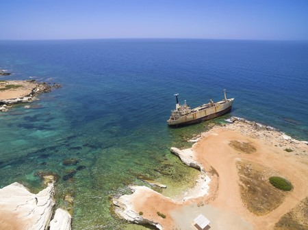 Aerial view of the abandoned ship wreck EDRO III in Pegeia, Paphos, Cyprus. The rusty shipwreck is stranded on the Peyia rocks at the kantarkastoi sea caves near Coral Bay in Pafos, standing at an angle near the shore. Stock Photo