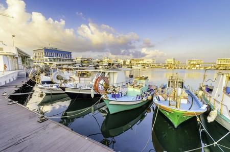 Fishing boats docked at the Limassol old port in Cyprus, next to the Marina. A view of the harbor, the mediterranean sea, the water, boat fish nets, equipment, restaurants and shops at sunset.