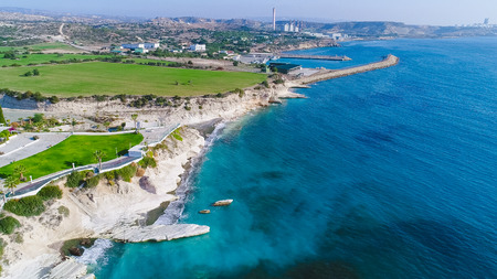 Aerial view of coastline and landmark big white chalk rock at Governors beach, Limassol, Cyprus. The steep stone cliffs and deep blue sea waves crushing in coves and dark sand next to Kalymnos fish restaurant from above and vasilikos power station in the background.