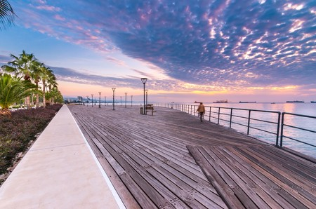 Molos Promenade and skyline of the coast in Limassol city in Cyprus at sunrise. View of the boardwalk pier path landmark with palm trees, pools of water, the Mediterranean sea and people walking. Stock Photo