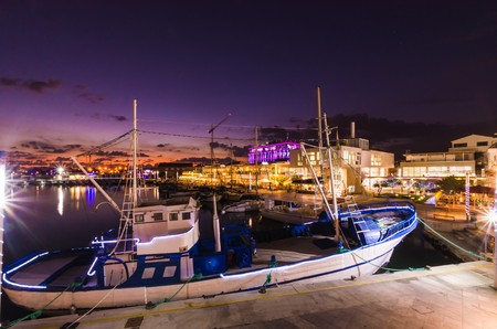 Fishing boat docked at the Limassol old port in Cyprus, next to the Marina. A view of the harbor, the mediterranean sea, the water, boat fish nets, equipment, restaurants and shops at sunset to dusk. Stock Photo