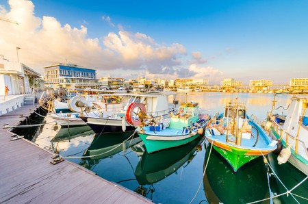 Fishing boats docked at the Limassol old port in Cyprus, next to the Marina part of the ports authority. A view of the harbor, the mediterranean sea, the water, boat fish nets, equipment, restaurants and shops at sunset.