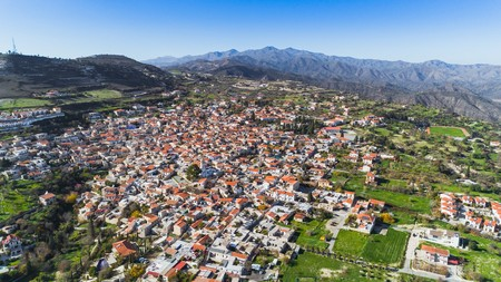 Aerial bird eye view of famous landmark tourist destination valley Pano Lefkara village, Larnaca, Cyprus. Ceramic tiled house roofs, greek orthodox church at south troodos hills, kionia, from above. Stock Photo