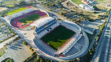 Aerial birds eye view of GSP football stadium and highway A1 at Latsia, Nicosia, Cyprus. The soccer field, athlete track, seats and auxiliary pitch of Pancyprian Gymnastic Association Stadium from above