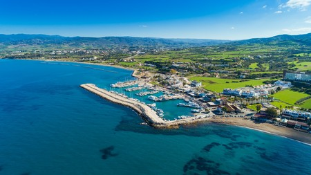 Aerial bird's eye view of Latchi port, Akamas peninsula, Polis Chrysochous, Paphos, Cyprus. The Latsi harbour with boats and yachts, fish restaurants, promenade, beach tourist area and mountains from above.