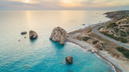 Aerial Bird's eye view of Petra tou Romiou, aka Aphrodite's rock a famous tourist travel destination landmark in Paphos, Cyprus. The sea bay of goddess Afroditi birthplace at sunset from above. Banco de Imagens - 94221804