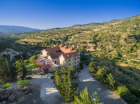 Aerial birds eye view of christian greek orthodox Holy Monastery of Panayia Amasgous in Monagri village, Limassol, Cyprus. The traditional stone ceramic roof tiled church in the forest slope from above.