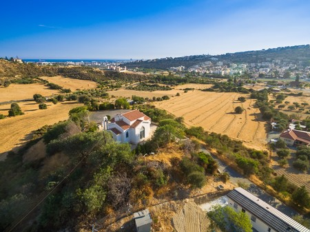 Aerial bird eye view of Saint George chapel (parekklisi Agiou Georgiou) in Germasogia municipality, Limassol, Cyprus on a hill by the sea inside hay fields at summer. A christian greek orthodox church.
