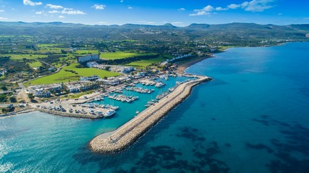 Aerial birds eye view of Latchi port, Akamas peninsula, Polis Chrysochous, Paphos, Cyprus. The Latsi harbour with boats and yachts, fish restaurants, promenade, beach tourist area and mountains from above.