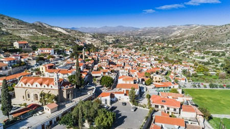 Aerial birds eye view of Kalavasos village valley, Larnaca, Cyprus. A traditional town with ceramic roof tiles a greek orthodox christian church and muslim mosque around hills from above. Banco de Imagens