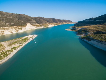 Aerial Birds eye view of artificial lake at the largest dam in Cyprus, Kouris reservoir, Limassol. View of the river split peninsula, earthfill embankment and hills around water from above. Banco de Imagens