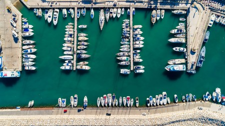 Aerial birds eye view of Latchi port, Akamas peninsula, Polis Chrysochous, Paphos, Cyprus. The Latsi harbour with boats and yachts aligned, fish restaurants, promenade, beach tourist area from above. Banco de Imagens
