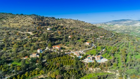 Aerial bird eye view of Miliou village hills and Akamas sea at Latchi, Paphos Cyprus. View of traditional ceramic tile roof houses near Ayii Anargyri monastery nature hotel spa from above. Banco de Imagens