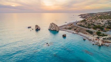 Aerial Birds eye view of Petra tou Romiou, aka Aphrodites rock a famous tourist travel destination landmark in Paphos, Cyprus. The sea bay of goddess Afroditi birthplace at sunset from above.