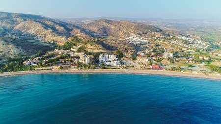 Aerial birds eye view of Pissouri bay, a village settlement between Limassol and Paphos in Cyprus. Panoramic view of the coast, beach, hotel, resort, hills, plain and building developments from above.